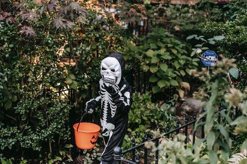 Frightening child in skeleton costume walking along garden with bucket