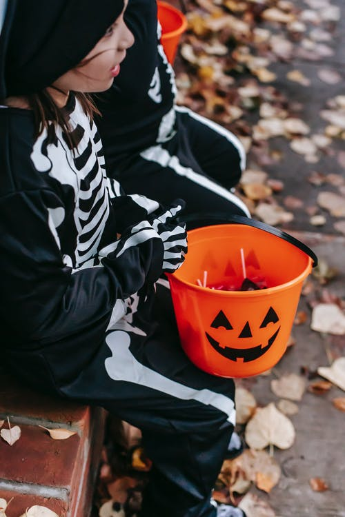 Crop little child dressed in Halloween costume sitting on bench with candy bucket