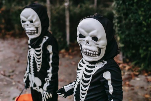 Unrecognizable people in costumes and masks of skeletons standing with bucket in autumn park