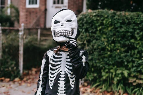 Crop faceless kid dressed in skeleton costume taking off scary mask while standing near house with fallen leaves and foliage on Halloween day