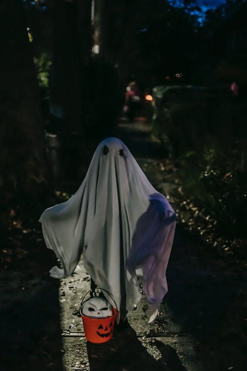 Anonymous kid dressed like frightening ghost standing alone on dark street between greenery with white mask in jack o lantern bucket during Halloween celebration