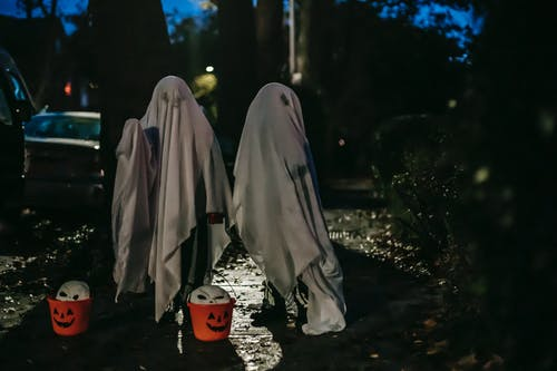 Unrecognizable children standing on dark street with buckets for trick or treat covered with white blankets painted like ghosts for Halloween celebration