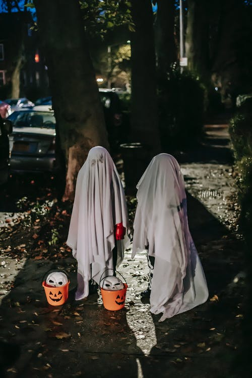 Orange buckets with masks placed near children in Halloween costumes at night