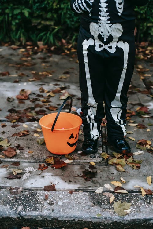 Crop anonymous child in Halloween scary costume standing on asphalt street with orange plastic bucket before trick or treat in daytime