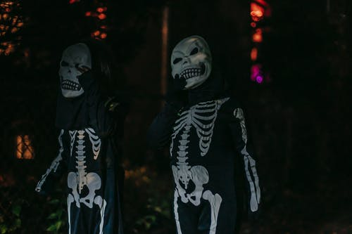 Unrecognizable persons dressed in costumes of skeleton standing on dark street