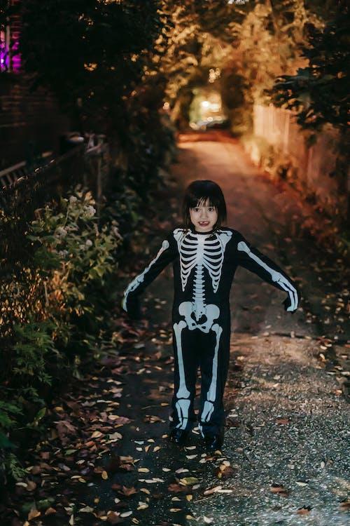 Cheerful cute little girl in Halloween skeleton costume in evening