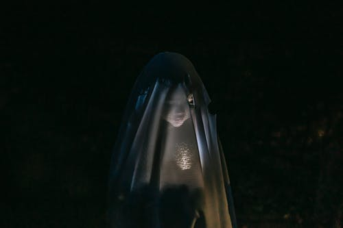 Mysterious little girl standing in darkness covered with white blanket as ghost and shining flashlight on face