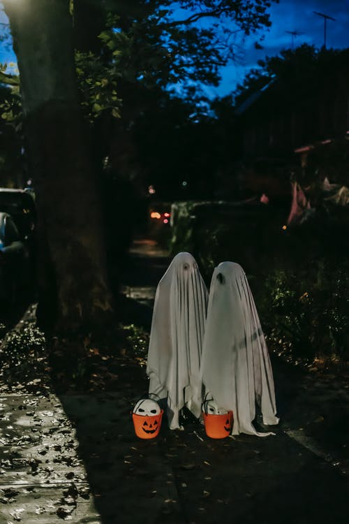 Unrecognizable kids in Halloween ghost costumes standing in shadow of illuminated tree