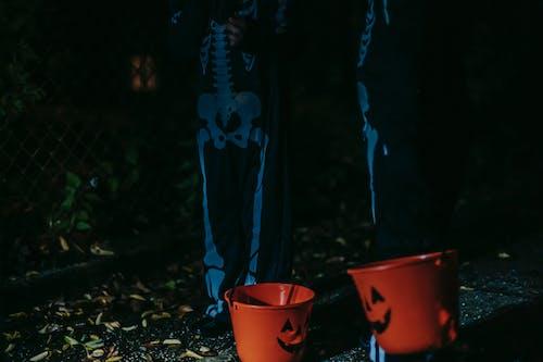 拿著紅色塑料桶的藍色和黑色外套的人