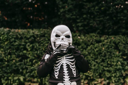 Unrecognizable child in skeleton costume for Halloween celebrating standing with hand near face in autumn street and looking at camera