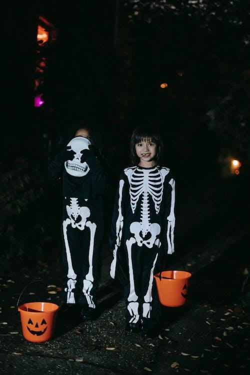 黑色和白色的長袖襯衫,站在夜間紅色塑料桶旁邊的女人