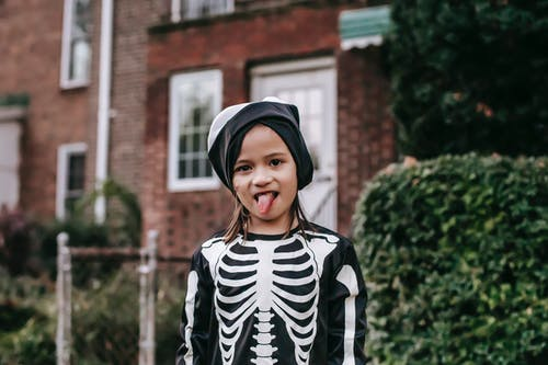 Funny girl in skeleton costume and mask on head showing tongue while standing on street in Halloween day and looking at camera
