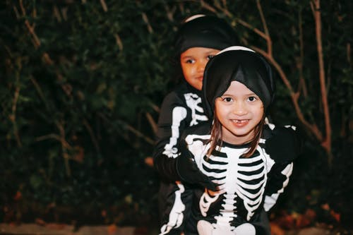 Happy diverse girls in skeleton costumes  and masks on heads embracing while having fun and smiling in Halloween night in park