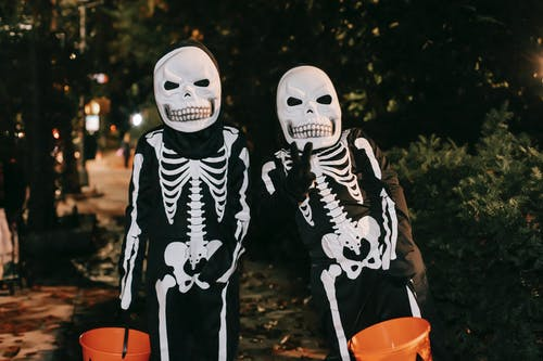 Spooky anonymous persons in skeleton costumes and masks with pumpkin buckets with sweets having fun on street in Halloween night and looking at camera