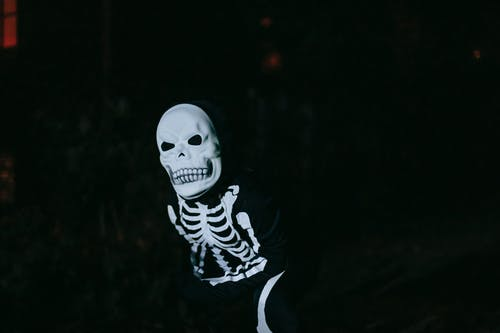 Unrecognizable kid in skeleton costume and skull mask having fun and frightening people in dark forest during Halloween celebration at night