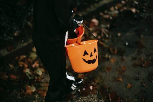 黑色連帽衫和黑色褲子,拿著黃色的塑料桶的人