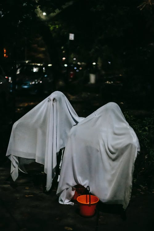 Unrecognizable children in ghost costumes on street