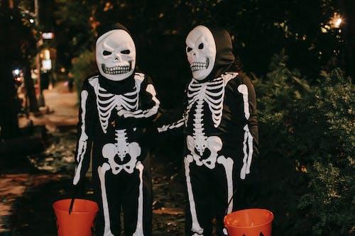 白色和黑色的骨架,拿著紅色的塑料桶