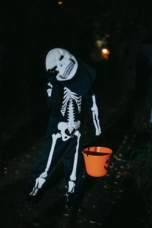 Unrecognizable kid in festive costume and mask with happy skull standing with tilted head and plastic bucket while touching eye at night