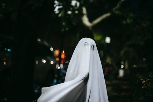 Faceless child in ghost costume on Halloween night in town