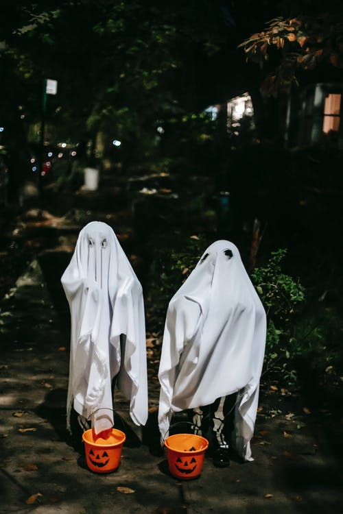 Unrecognizable kids in ghost costumes with plastic buckets in form of carved pumpkins celebrating festive event in night city