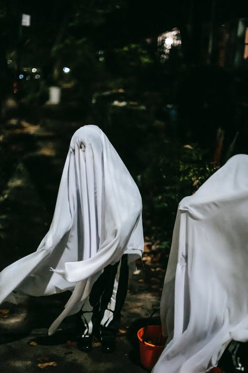 Unrecognizable children wearing spooky ghost costumes while playing together and having fun in lush park