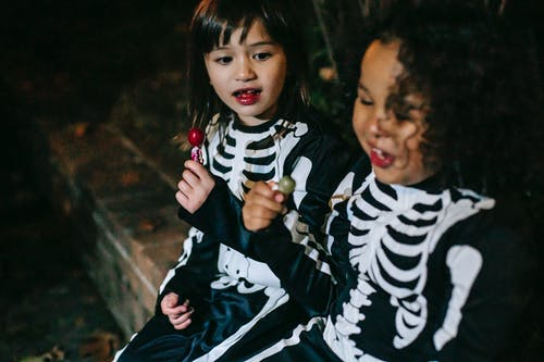 Crop happy diverse girls in skeleton costumes enjoying stick candies