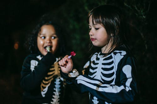 Content multiethnic girls in skeleton costumes eating stick candies