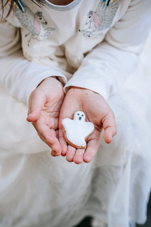 From above crop girl wearing stylish white dress showing sweet gingerbread ghost cookie on hands during Halloween celebration