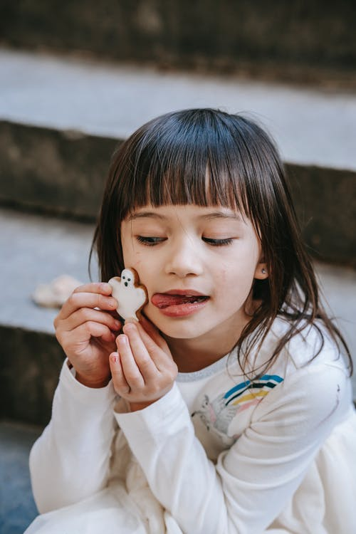 Adorable ethnic girl holding traditional ghost cookie near pretty face