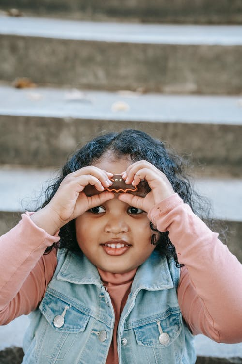 Cute happy ethnic girl in casual wear holding scary bat gingerbread cookie against forehead while sitting on staircase and looking away during Halloween celebration
