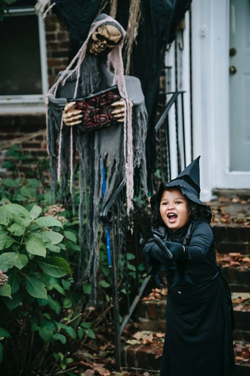 Joyful girl in witch costume standing near Halloween decorations