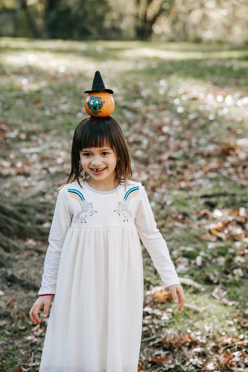 Cute happy girl in white dress carrying small Halloween pumpkin on head in October park