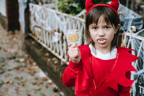 Little girl in devils costume demonstrating stick candy in park
