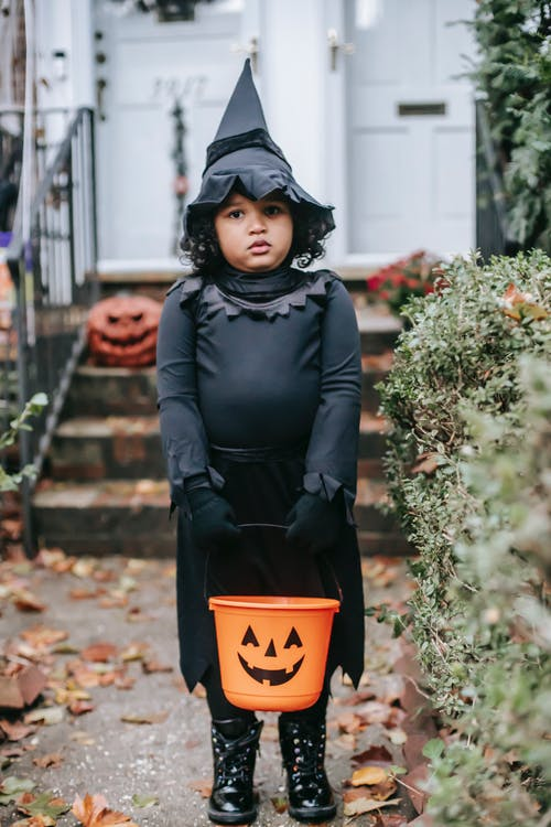 Full body little ethnic girl wearing witch costume standing with Trick or Treat bucket near cottage entrance and looking at camera