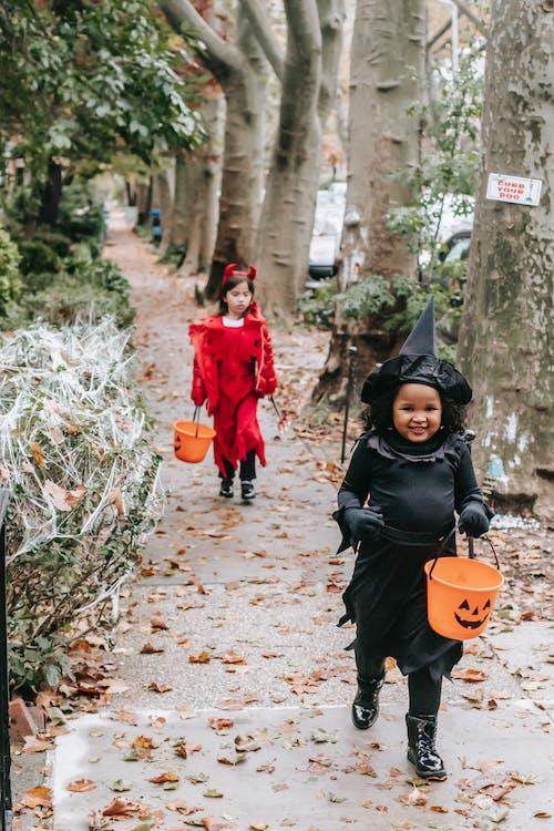 Cheerful cute girls in Halloween costumes walking in autumn park