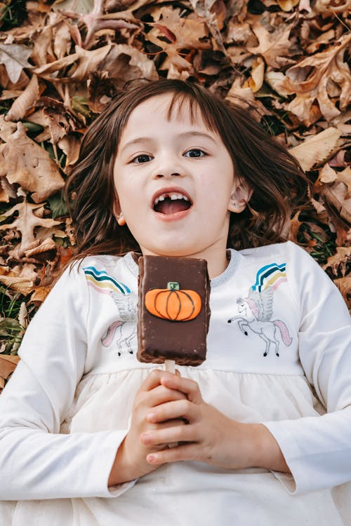 From above happy little girl enjoying chocolate ice cream decorated with pumpkin while lying on fallen autumn leaves and looking at camera merrily