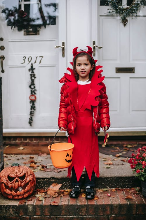 Full body positive little girl wearing red devil costume with Trick or Treat bucket standing on doorsteps with Halloween decorations and looking at camera