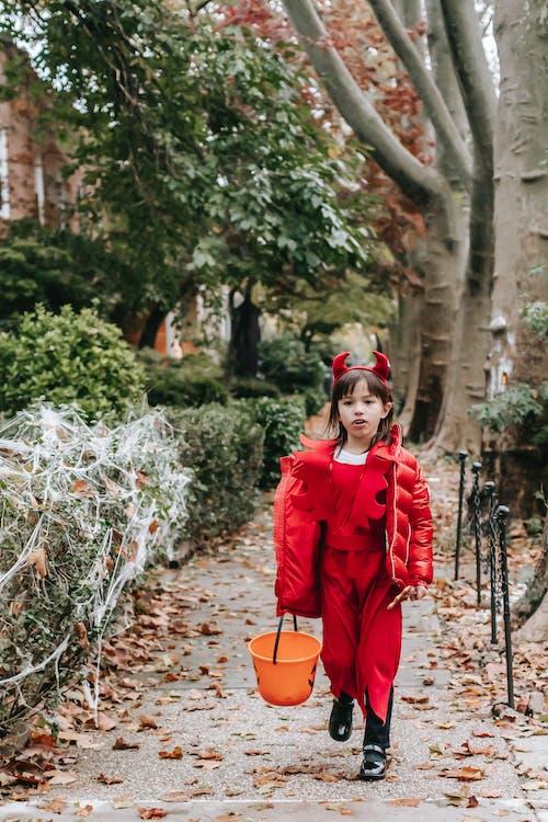 Little girl in devil costume strolling on sidewalk