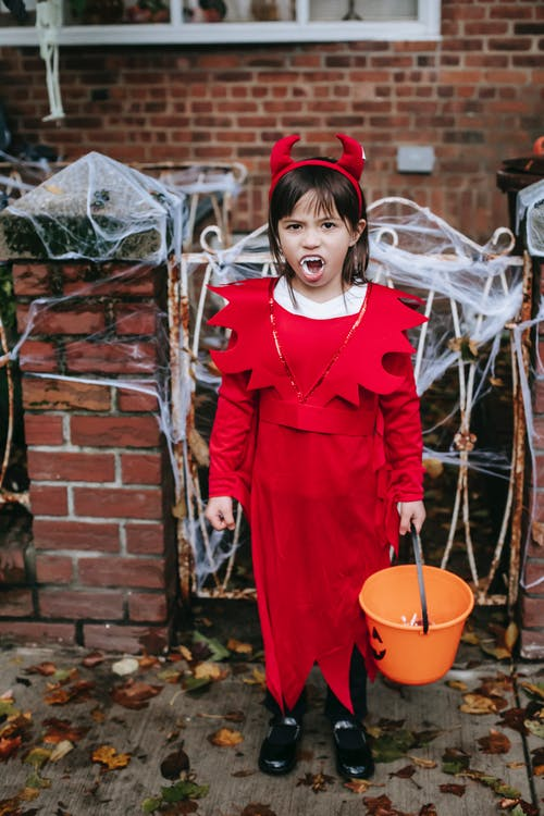 Girl in devil costume standing with Trick or Treat basket