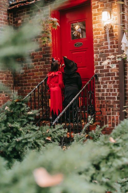 Unrecognizable kids in Halloween costumes knocking on house door