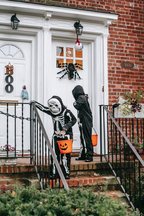 Man in Black and White Skeleton Costume Standing on Brown Staircase