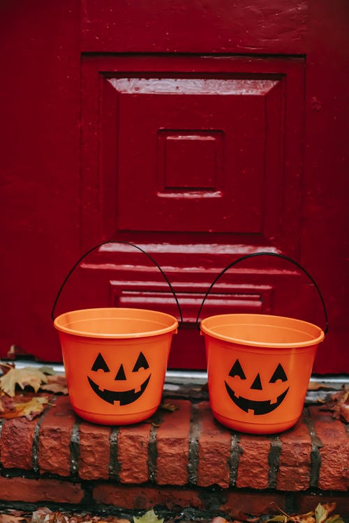 Bright orange pumpkin buckets for Trick or Treat game placed on doorway during Halloween celebration