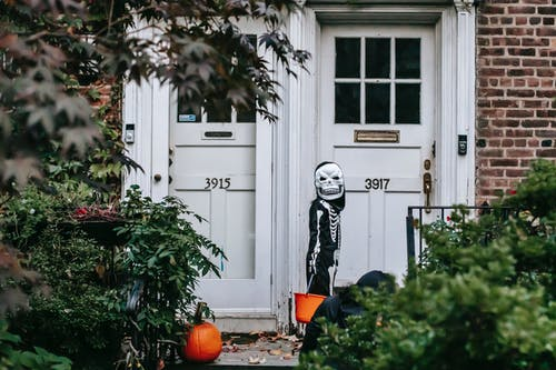 Person in Black and White Skeleton Costume Standing Near White Wooden Door