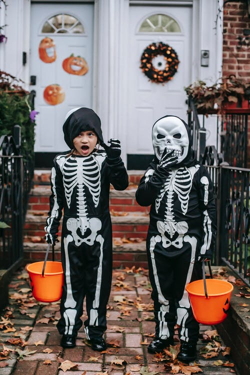 2 Boys in Black and White Skeleton Costume Standing Beside Brown Concrete Wall