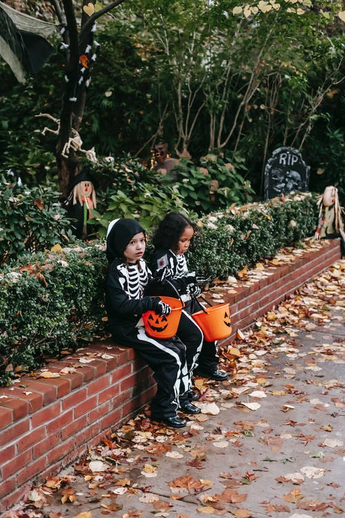 Multiethnic kids in Halloween costumes sitting in street