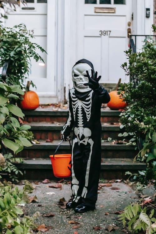 Unrecognizable child in Halloween costume standing with bucket in street
