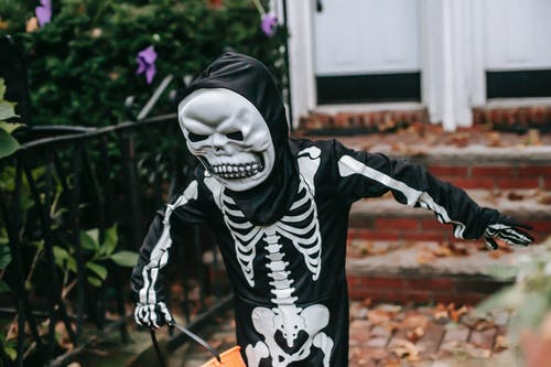 Person in Black and White Skeleton Costume Holding Brown Stick