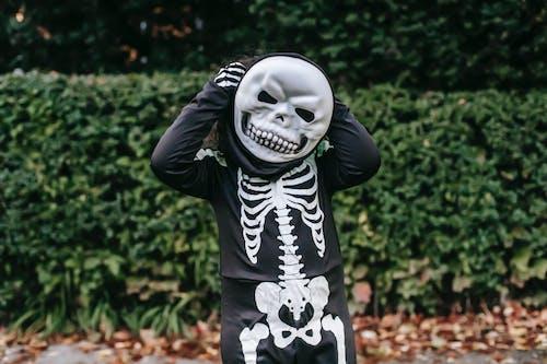 Unrecognizable kid wearing skeleton costume on Halloween