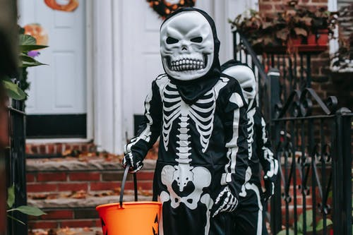 Person in Black and White Skeleton Costume Holding Red Plastic Bucket